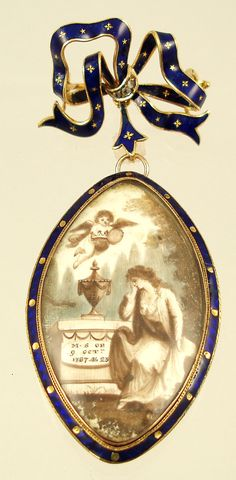 Georgian navette-shaped brooch dated 1787.  Hand-painted sepia miniature on ivory of a woman mourning at the tomb with an angel hovering above.  Accented with dissolved hair, inscribed on the tomb: M.S. OB 9 OCT 1787 AE 23.  G. Selleron inscribed on reverse. 9-10K gold mounting with cobalt blue enamel surround.