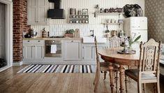 habitacion vintage, cocina con paredes de ladrillos, suelo de parquet, mesa oval y sillas de madera vintage