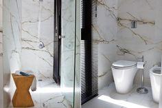Un baño lleno de luz natural, con paredes y piso en símil mármol. Foto: Santiago Ciuffo