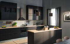 Tumma ja tyylikäs KUNGSBACKA-keittiö, jossa puiset tasot ja tyylikkäät mattamustat pinnat