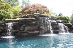 Water Feature Swimming and Landscape  in Bergen County NJ : Backyard landscaping and water feature swimming pool in Saddle River, Bergen County , NJ.   The man made waterfalls are constructed of Pa. colonial boulders.  The centerpiece plantings is an Acer palmatum dissectum (lace leaf maple).  The boulders are covered with stonecrop sedum.