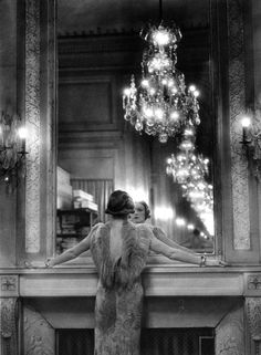 Model pausing to regard herself in the grand mirror of the Molyneux atelier. Paris, France, 1934