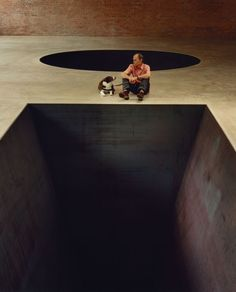 """Heizer with his sculpture """"North, East, South, West"""" and his dog Tomato Rose."""