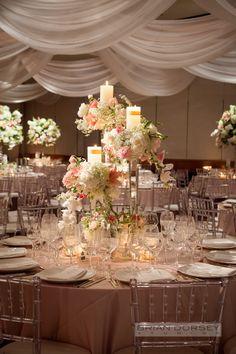 Centro de mesa con velas y flores en distintas alturas para darle más profundidad a la decoración. #CentrosDeMesa