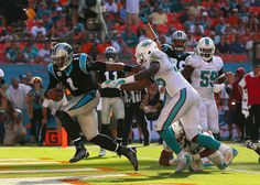 Cam Newton #1 of the Carolina Panthers rushes for a touchdown during a game against the Miami Dolphins at Sun Life Stadium on November 24, 2013 in Miami Gardens, Florida.