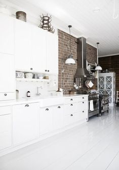 Finnish farmhouse - Stainless Steele on brick background, white painted wide plank wood floor, pulls on white cupboards