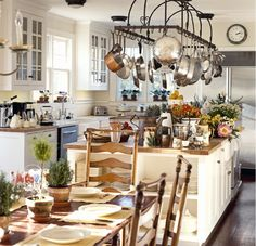 Designer Robin Bell knows the importance of a big, dynamic kitchen island. For this New York cottage she opted for a piece that had bonus storage on the sides and an extensive pot rack on top.   - HouseBeautiful.com
