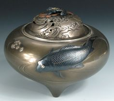 A tripodic shibuichi koro with a bronze koi swimming downstream, its inlaid eyes gilt and its body and scales modeled in relief.  Maiji period