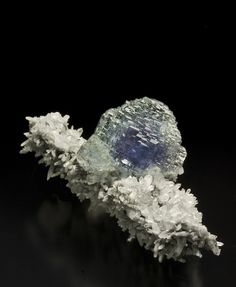 mineralogy-porn:  A spire of matrix, covered by Quartz needles, hosts a lustrous Fluorite crystal with zones of light green, purple, and blue.  Oh, wow.