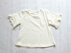 White+cotton+girls+top+with+ruffled+3/4+sleeves.+The+sleeves+also+have+a+lovely+crochet+detail.+The+round+neck++meets+at+a+peep+loop+in+…