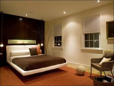 A wood wall is the backdrop for this modern bedroom. Cove lighting ...
