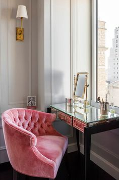 Gorgeous and serene corner home office.... Lovely detailed trim work, accented by the gold sconce.... And the perfect pairing of a plush, pink chair and soft grey walls.
