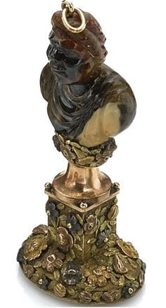 vari-colored gold and hardstone desk seal, circa 1830, the handle formed as a carved blackamoor bust, the pedestal and cushion applied with flowers and leaves, the bloodstone matrix incised with a profile portrait of a classical maiden.  image Sothebys