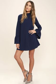 The Mod Squad Navy Blue Shift Dress is the perfect addition to your crew of on-trend pieces! Lightweight poly shapes a mock neck and fun, tying open back. Long bell sleeves and a shift silhouette complete the look.