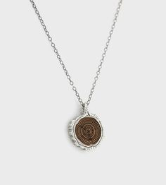 This small pendant features tree rings etched on chechen or swiss pear wood. Hanging from a delicate brass or silver chain, the colors of the wood inlay contrast beautifully against the pendant.