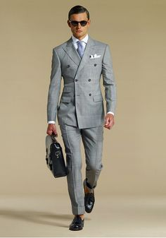 Double-breasted grey checked suit, white shirt, light blue tie. Accessories black shades, briefcase.