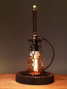 "Rusty Remakes Signature ""Oil Rig"". A light bulb resting on an industrial cog, held in place by brass chains, attached to a rusty metal part from a Swedish milk separator. An industrial spring and a brass ball crowns the design, completing the look of an upside down torch."