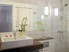 Hvite fliser dekker hele baderommet, bortsett fra rundt vasken og bortover hyllekanten. Her har de valgt å bryte opp med brune fliser.