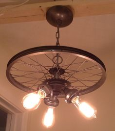 We created this bike rim chandelier from the wheel of an old bike. (17 diameter) It also includes various vintage light fixtures and lamp parts.