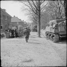 Sherman tanks of the 5th Canadian Armoured Division and infantry of the 11th Royal Scots Fusiliers, 49th (West Riding) Division, advance through the outskirts of Ede in The Netherlands, 17 April 1945.