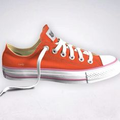 A custom Chuck Taylor converse sneaker. Orange with yellow inside and a 'lucky' ID
