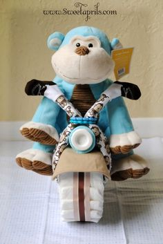 diaper motorcycle gift. Made out of diapers, baby clothes, and stuffed animal. Like the diaper cakes. how cute.