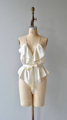 Vintage 1980s, early 1990s ivory satin teddy with ruffled V neckline, spaghetti straps, elastic waist, self-fabric tie belt and snaps between the legs. ✂-----Measurements fits like: small/medium bust: 38 waist: 25-31 length: 32.5 brand/maker: Victorias Secret condition: excellent to ensure a good fit, please read the sizing guide: http://www.etsy.com/shop/DearGolden/policy ✩ more lingerie | swim ✩ https://www.etsy.com/shop/DearGolden...