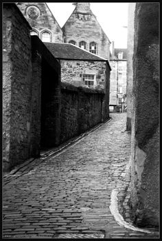 Black and white photograph of a time gone by in Edinburgh Scotland. The image provides a snapshot of a late 18th century cobblestone street and buildings nestled in the modern world.  I actually fell down on my bike avoiding a car while riding down this alley.