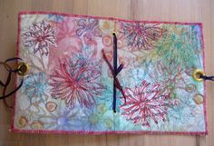 DIY: painted journal cover tutorial by Jane LaFazio. made with unprimed artists canvas, spray gesso, Luminarte twinkling H2Os, hand carved stamps, grommets and sewing machine #mixed_media #handmade_books #art