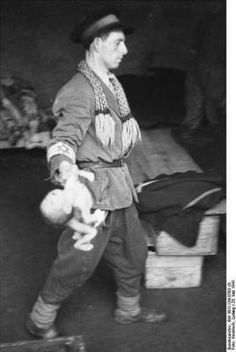 A Jewish man carries a dead baby to a dead body collecting point. 25 May 1941. SAD SAD SAD