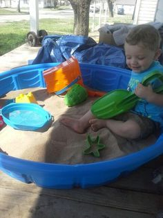 Easy and cheap sandbox. Buy a $9.88 kiddie pool from Walmart, add 3 50lb bags of sand, beach toys, and toss in your kid. Hours of entertainment.