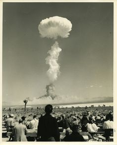 AEC-52-4474  ATOMIC TEST SITE, YUCCA FLAT, NEVADA, APRIL 22, 1952…Mushroom cloud rises over Yucca Flat, as dust cloud begins to form below.  In the foreground are some of the nearly 200 press, pictorial, radio, and TV representatives who observed the explosion. Credit: U.S.A.E.C.