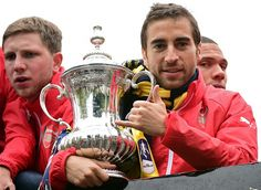 Arsenal's French midfielder Mathieu Flamini holds the trophy on the top deck of an open-topped bus during the Arsenal victory parade in London on May 31, 2015, following their win in the English FA Cup final football match on May 30, 2014 against Aston Villa. Arsene Wenger's side made history at Wembley with a 4-0 rout of Aston Villa that underlined their renaissance in the second half of the campaign and served as a warning to English champions Chelsea. AFP PHOTO / LEON NEAL