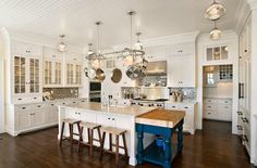 Amazing seaside kitchen with glossy white beadboard ceiling, floor to ceiling glass-front white kitchen cabinets with marble countertops, farmhouse sink in kitchen island, sawhorse stools, drop-down cobalt blue kitchen island with butcher block countertop, blue glass subway tiles backsplash, schoolhouse pendants and stainless steel pot rack.