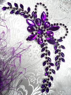 XR127 Deep Purple Crystal Rhinestone Applique Beth Embellishment    Size 7.5 x 2.5    The leaves on this applique are very flexible.    This applique is absolutely stunning with sparkle and design!    This applique is made of large high quality acrylic and Glass rhinestones.   Beautiful Victorian Design with a very rich, deep purple color.    Metal Flexible backing.    Great for sewing and craft projects.    Use on bridal gowns  wedding dresses  ice skating costumes  belly dancing costumes…