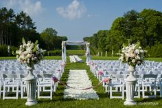 Elegant and feminine outdoor ceremony at the Crane Estate in Ipswich with white garden chairs, an aisle covered with white rose petals, huge floral arrangements in urns, and a beautiful chuppah with flowers and white silk.   Artistic Crane Estate Wedding Photography by Studioatticus – Studio Atticus