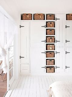 Lovely Storage!!  White on white interior - Oversize Hinges on Closet - Wicker Baskets in Cubbies.  Australian House and Garden