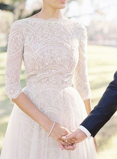 Lace wedding dress with diamond engagement ring and two dainty bracelets holding hands with groom