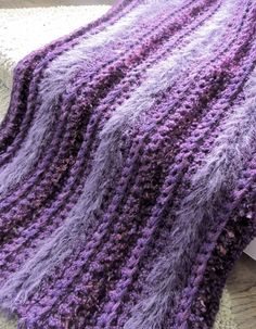Crochet throw - a work in progress and nearly finished. I started out using left over yarns but of course needed to buy more. All done in single crochet, I used Sashay (scarf yarn), Bernat Boa eyelash, Homespun Grape, Loops & Threads fabulous fur as well as a L&T sequin yarn to trim. Unfortunately the metallic from the Sashay doesn't show in the photo. Can't wait to fringe this one...it's so soft and cozy!