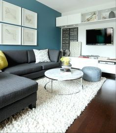 Cutler Design Construction: Peacock blue accent wall, white square gallery frames, charcoal gray linen sectional, moroccan pouf
