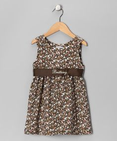This breezy little dress features covered button closures at the shoulders, precious pleating along the skirt and a sash across the waist that can be personalized with the name of the sweetie who's wearing it.