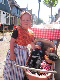 Meisje uit Urk met poppenwagen en poppen in dracht
