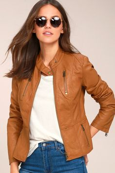 There is nothing quite like the open road and the Peace of Mind Tan Vegan Leather Moto Jacket! Sleek vegan leather shapes this unique moto jacket with a collarless silhouette and snap neckline. Antiqued gold front zipper with matching zippered pockets and cuffs complete the look.