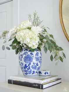 white hydrangeas in a blue chinosserie vase decorating with coffee table books fall flowers with seeded eucalyptus fall decorating-1