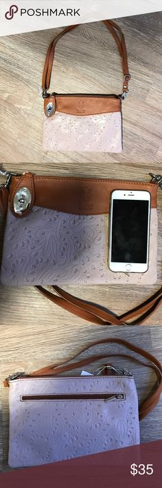 Italian leather handbag Brand new genuine Italian leather bag, cream color with a paisley patter, trimmed in camel brown with an adjustable camel strap and silver fixtures. Approximately 10x7 inches, pictured with an iPhone 6, the purse would go well cross body or over the shoulder. The bag opens with one zipper across the top and has an inside zipper pocket and an extra zipper pocket on the back.  I received this purse from family who visited Florence this fall, it's just not my style. Bags…