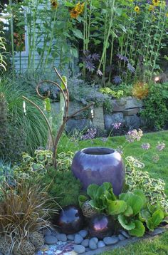 I like the combination of the urn, bergenia, variegated geranium, perennial grass, shiny balls, and rocks. Garden elements in the landscape |Lovely Collection