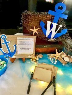 Found a box that looked like a treasure chest and adorned it with costume Jules and seashells. The monogrammed anchor was painted as it was two separate pieces and then glued it together. The couple can take it home and hang it on their front door at their Beachhouse. Also the display stand asked guests to give advice and write it down and place it in the box. The couple can take it home with them and read the lovely thoughts their guests wrote to them.