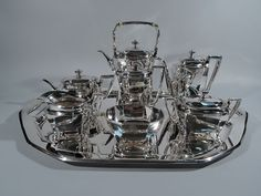 Only one in stock of this item shown.  Tiffany Art Deco Sterling Silver Tea & Coffee Service on Tray Art Deco sterling silver coffee and tea set on tray. Made by Tiffany & Co. in New York, ca 1907. This set comprises tea kettle on stand, coffeepot, teapot, hot water pot, creamer, sugar, and waste bowl on tray. #ArtDecoTeaAndCoffeeService #SterlingSilverTeaAndCoffeeService #TiffanyTeaAndCoffeeServices