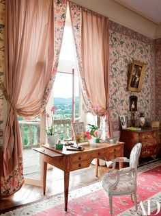 An 18th-century desk stands at a window in the summer master bedroom; the curtains are made of Braquenié fabrics, and the flowered wallpaper is 19th century | archdigest.com