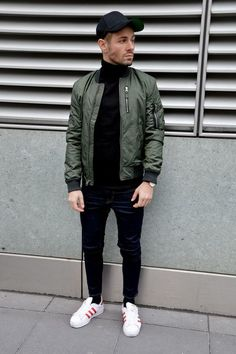 Green Bomber Jacket styled with Black Sweater, Denim Jeans and round off this look by wearing White Sneakers
